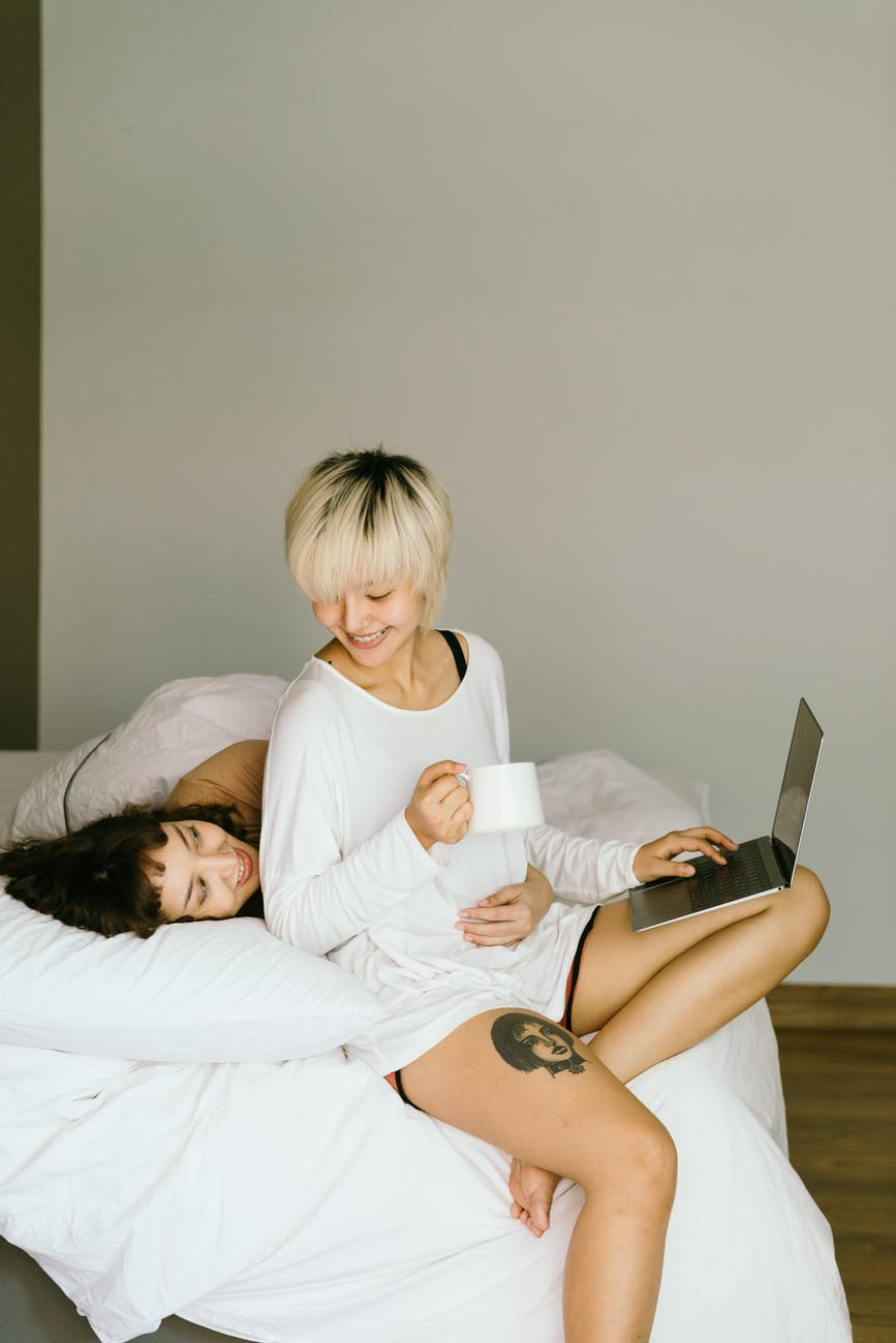happy lesbian couple hugging and browsing laptop on bed