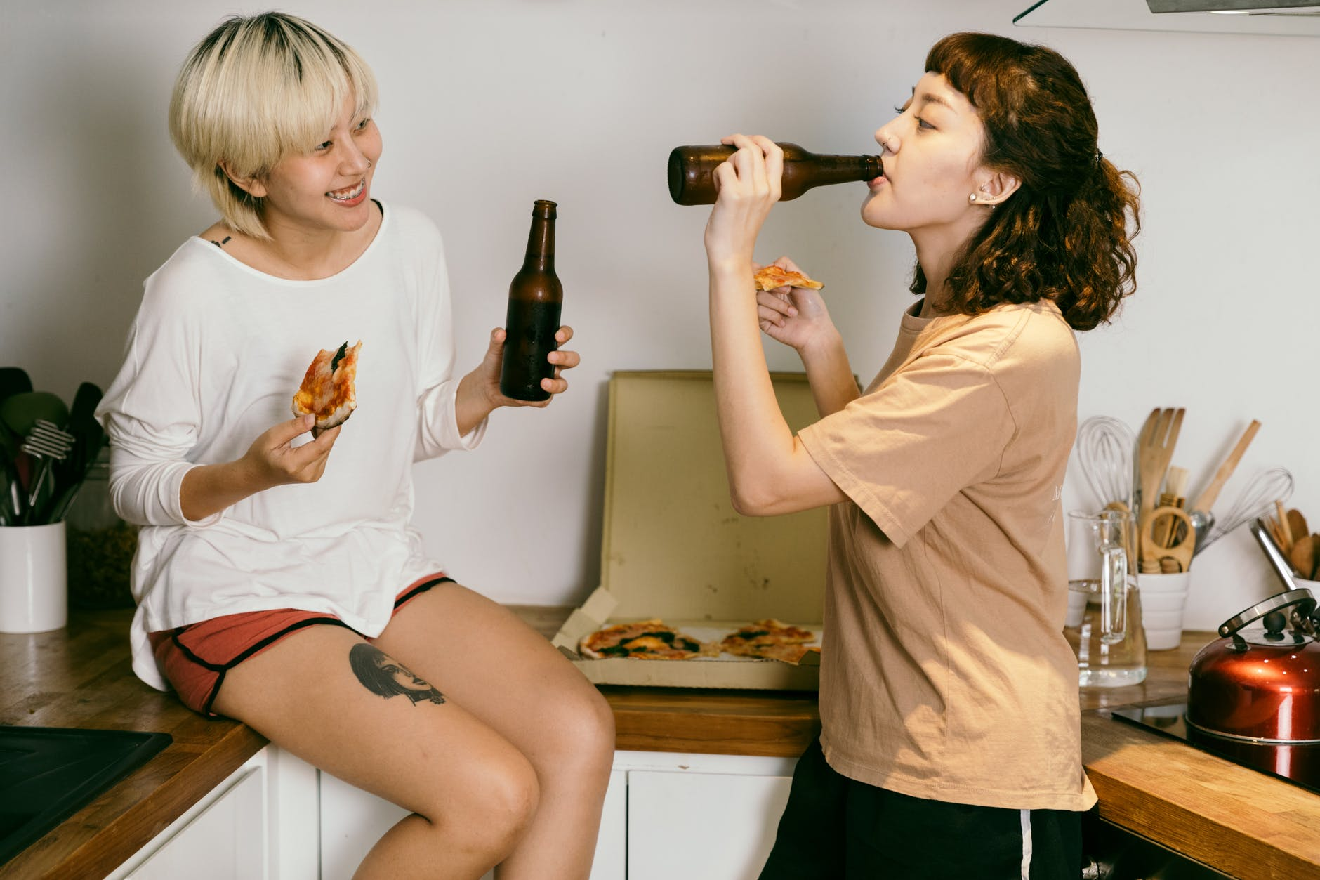 girlfriends eating pizza and drinking beer in kitchen at home